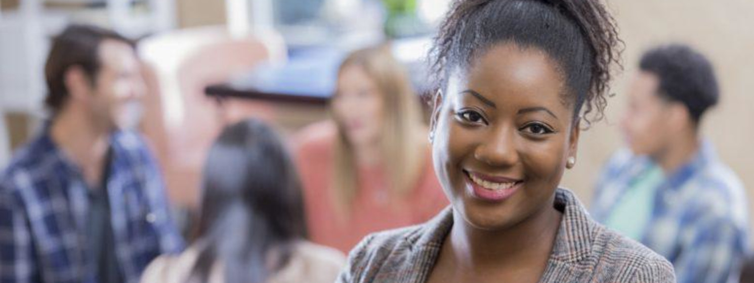 African-American behavioral health professional smiles while group meets behind her