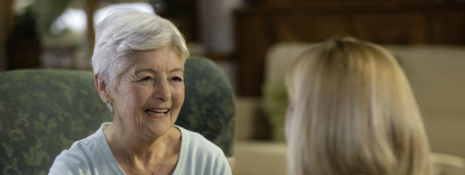 Older woman with short white hair smiles at a doctor in front of her
