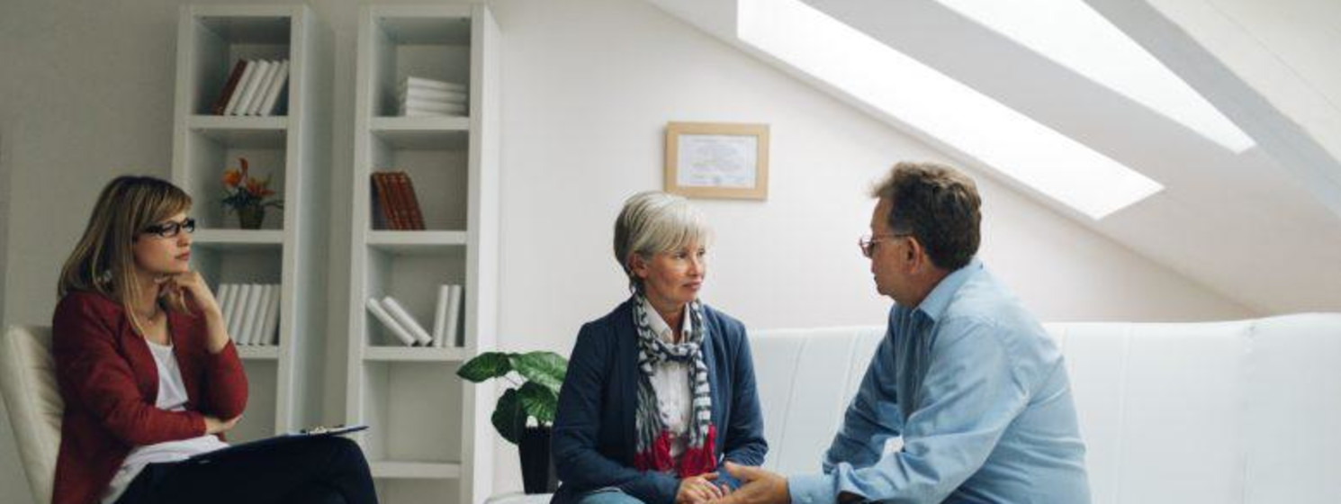 Female counselor observes older couple talking to each other face to face on white couch