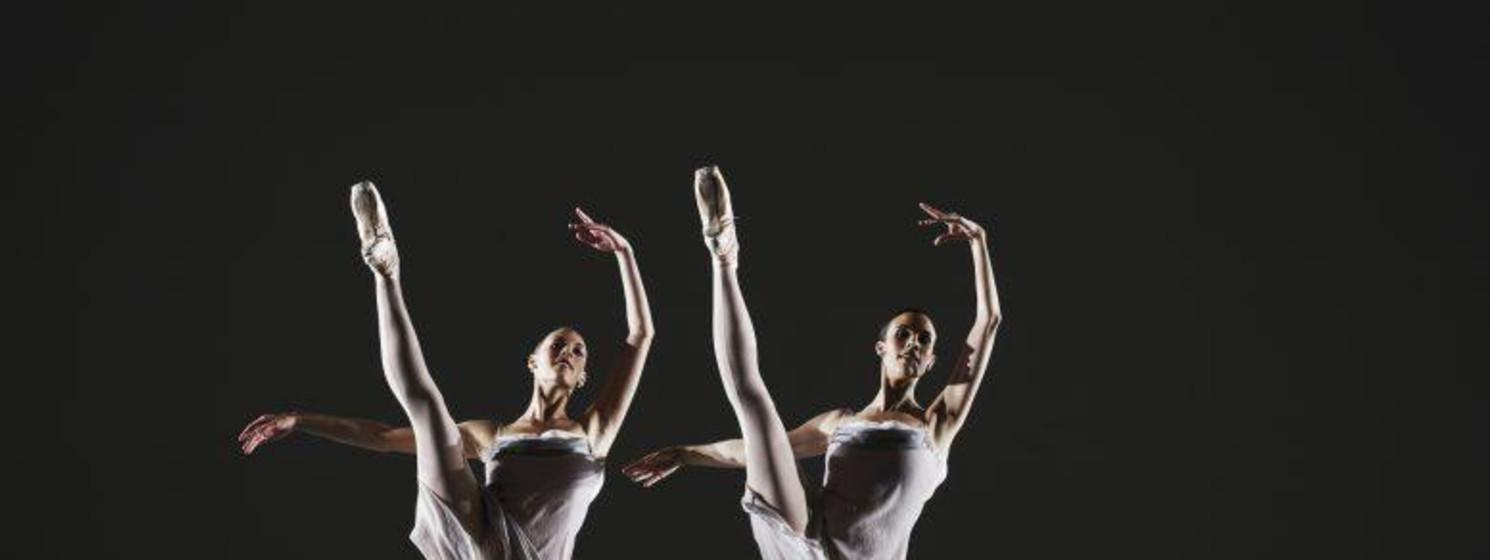 Two ballerinas dancing on stage, legs raised