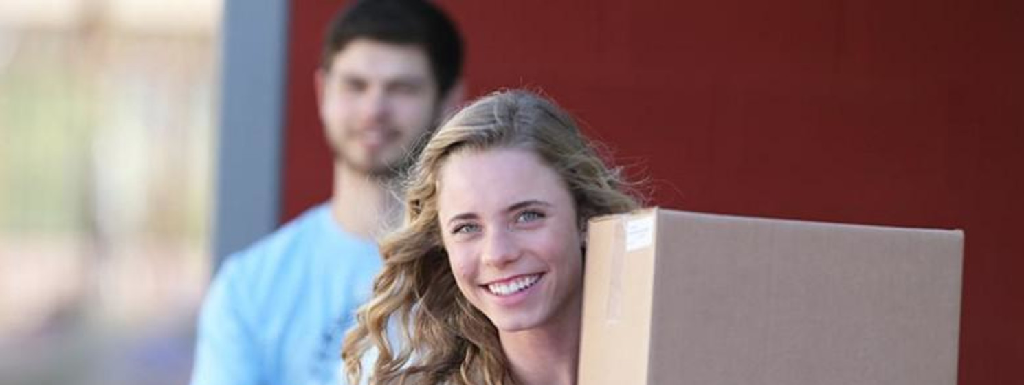 Woman and a man carrying boxes