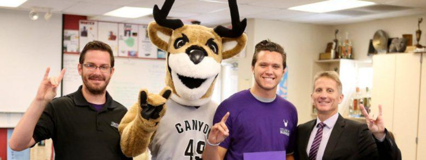 gcu mascot and three people smiling