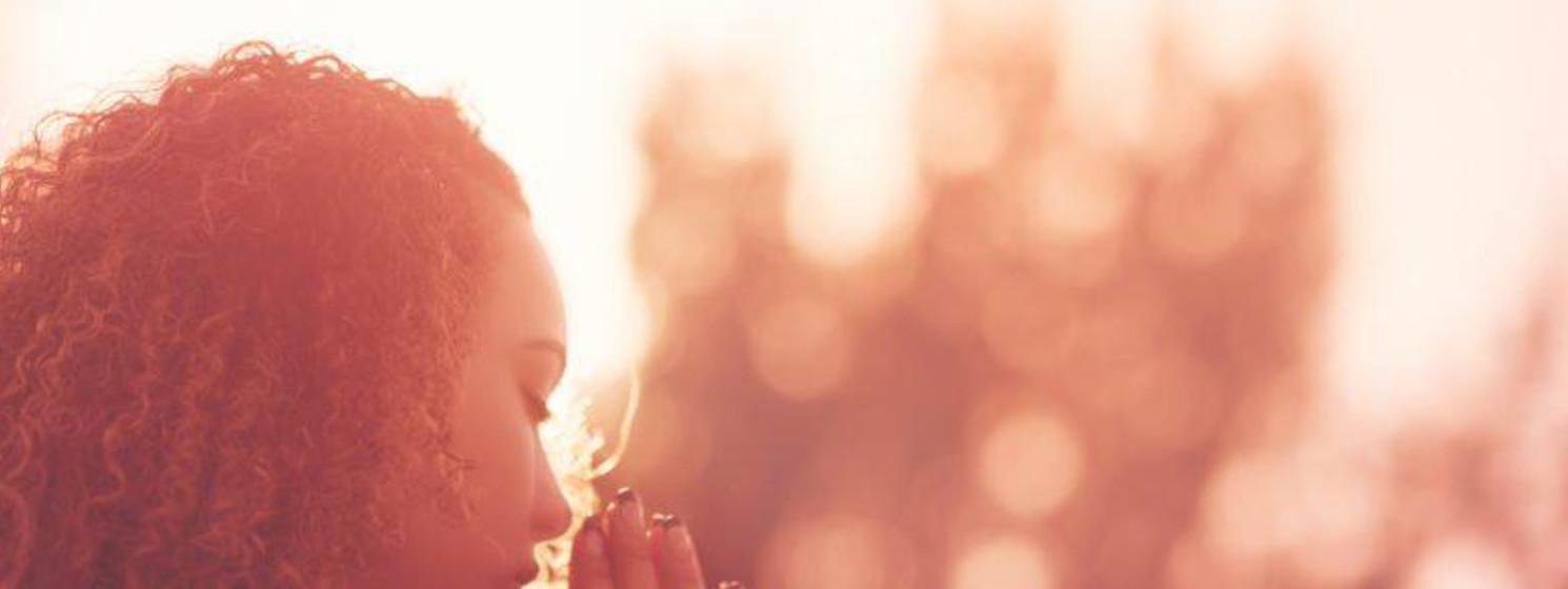 woman praying in the sunlight