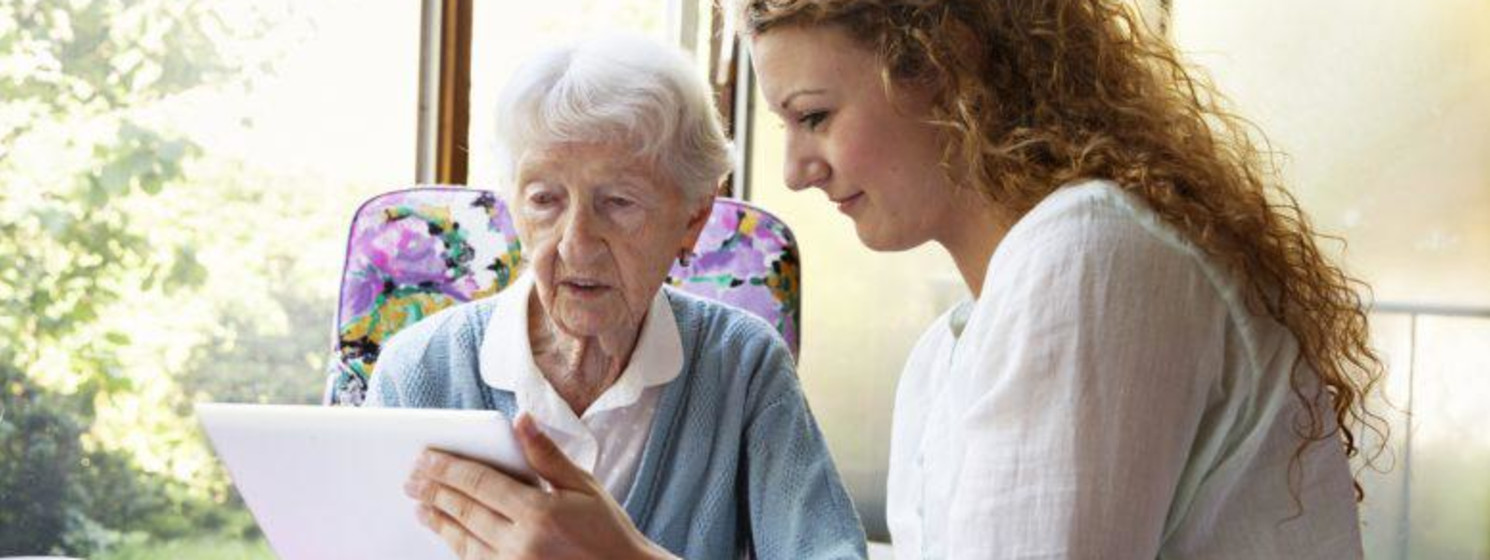 Woman with long curly hair shows elderly woman something on tablet