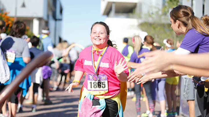 A little girl runs across the finish line wearing a gold cancer-fighting superhero cape