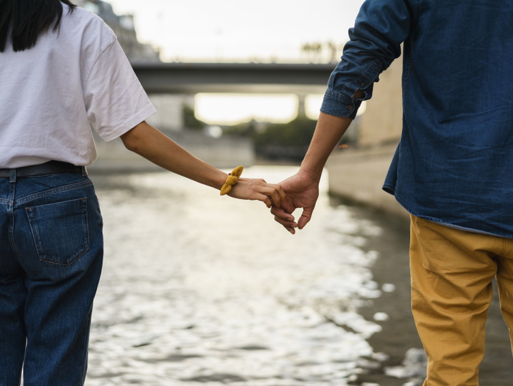 Couple holding hands by river