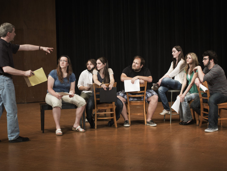 Students engage in a group activity in a theatre class setting