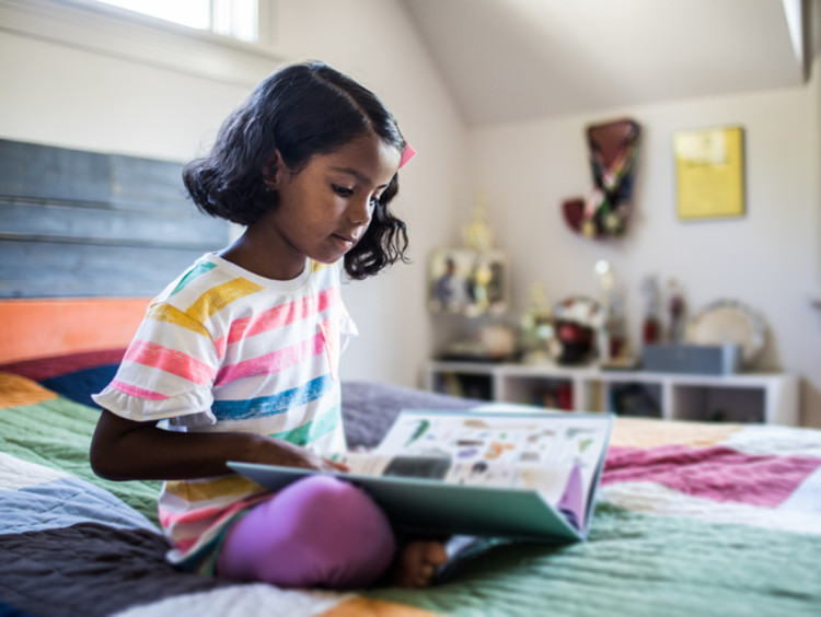 a child reading a book on her bed