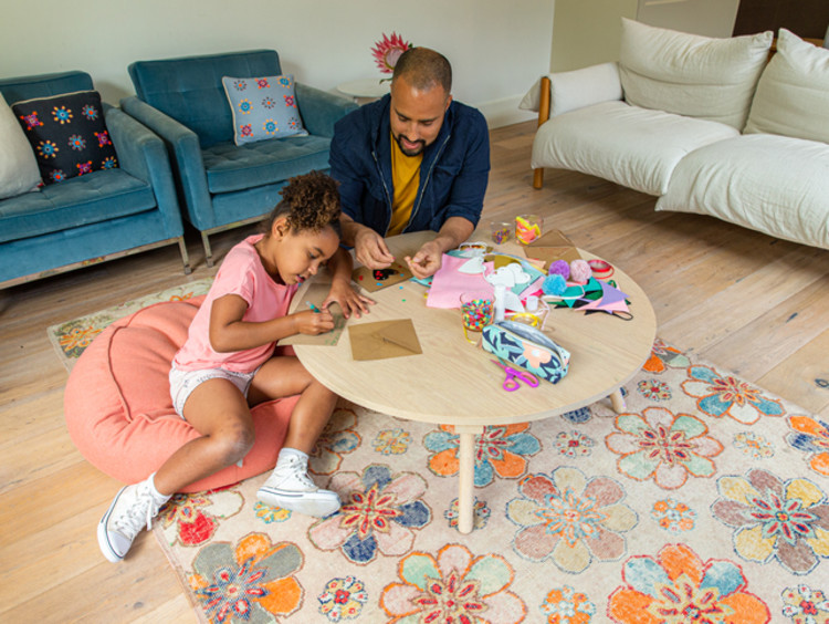 a child and her father doing crafts together