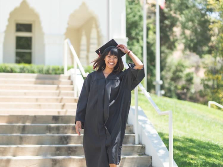 a college student on graduation day wearing a cap and gown