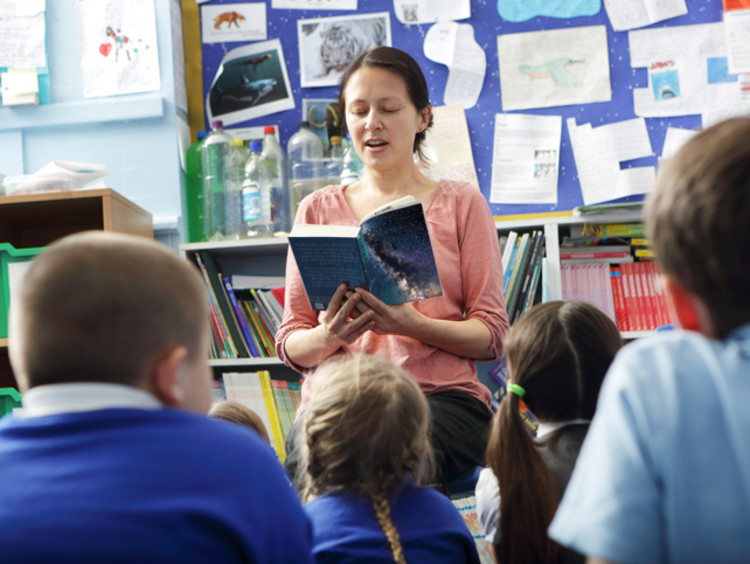 a teacher reading to elementary students