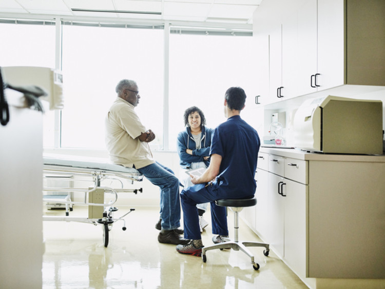 Nurse speaking with man sitting on hospital bed and woman sitting beside bed in hospital room