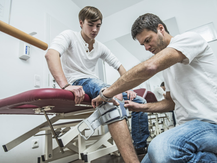 physical therapist looking at a patient's knee