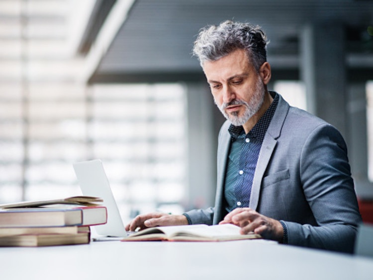 businessman studying a book outside