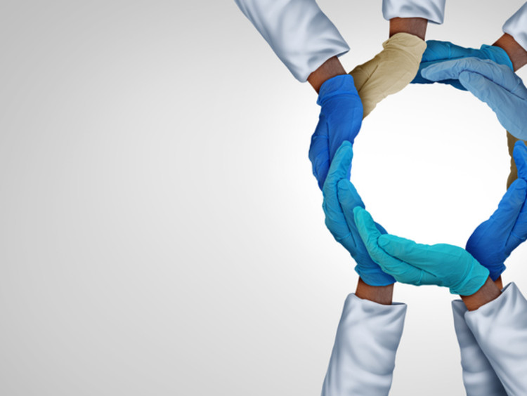 Doctors and nurses forming hands together in circle
