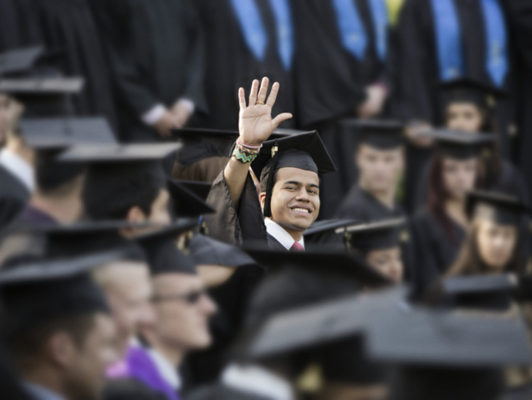 college student waving at graduation
