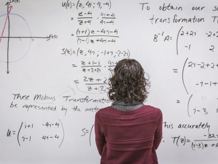 math teacher facing the board in reflection