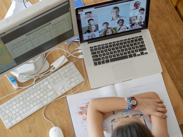 student attending class through a video call on a computer