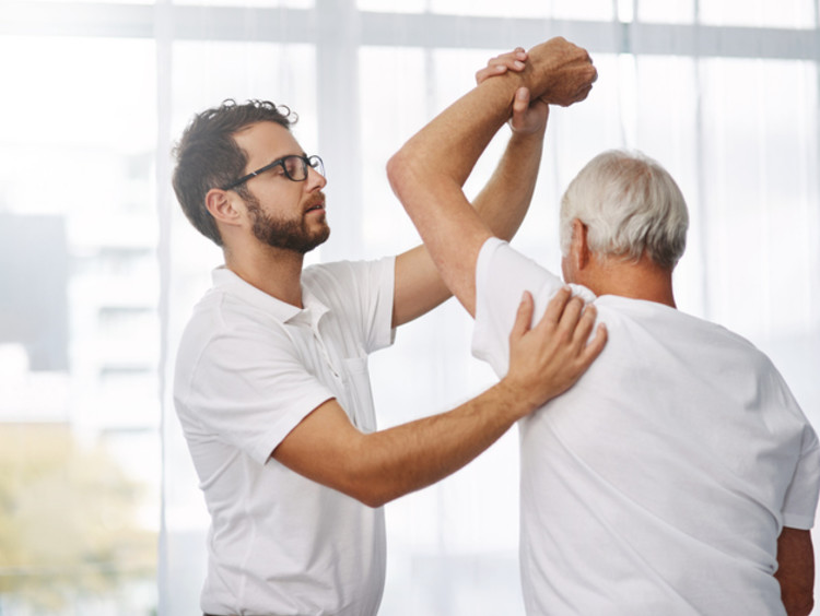 physical therapist helping an elderly patient