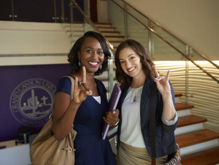 Two ladies give Lopes Up sign inside a GCU building