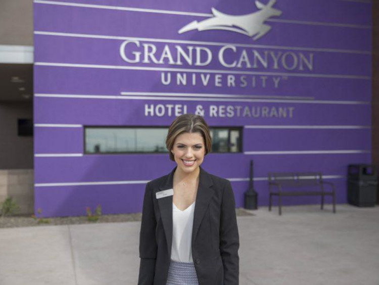 young woman in a blazer standing in front of the GCU hotel front desk