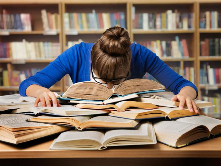 person with head in books