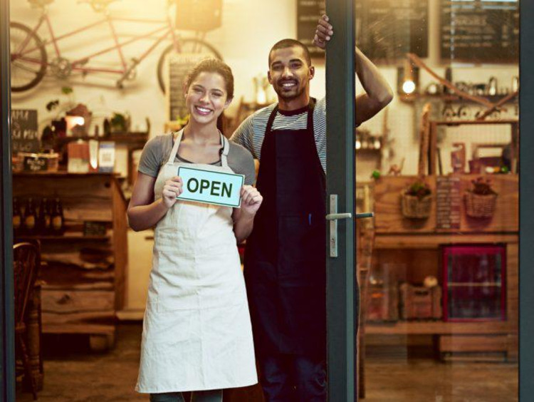 Couple stands in doorway holding a open for business sign