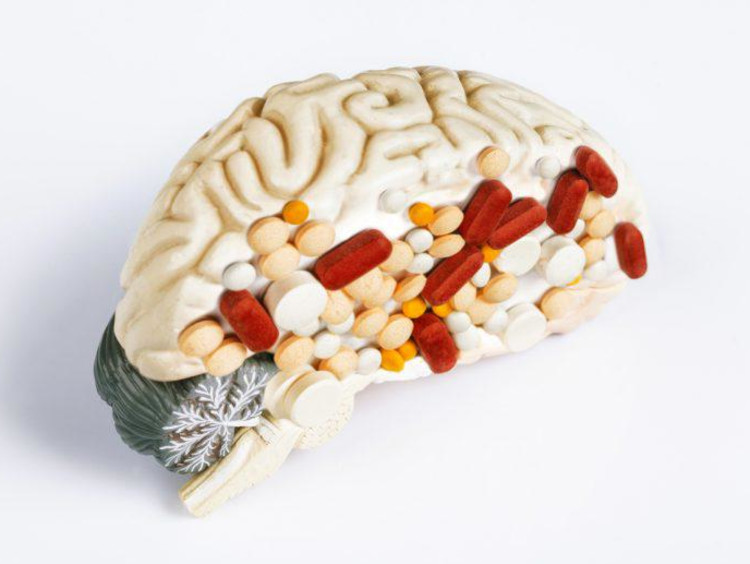 Half a model brain with pills stuck on it to resemble addiction