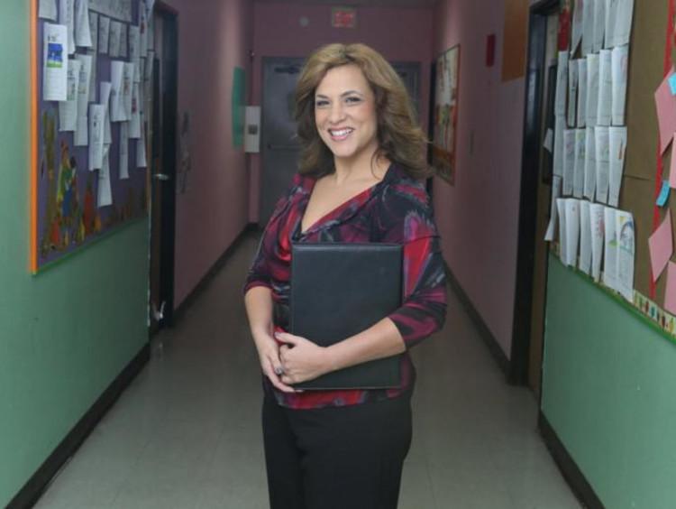 Smiling woman holds folder in school hallway