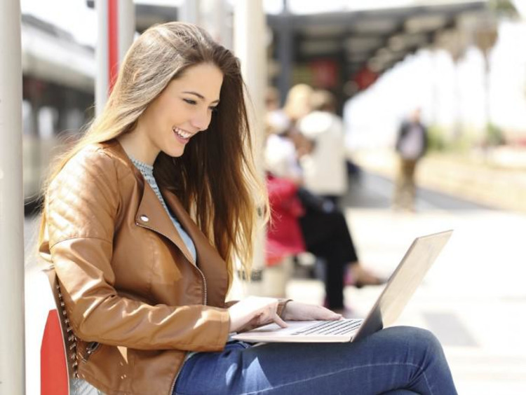 Young brunette woman smiles while using laptop at light rail station