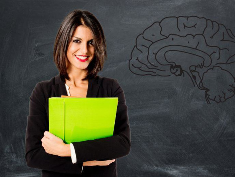 Confident business woman holds bright green folder in front of chalkboard with a brain drawn on it
