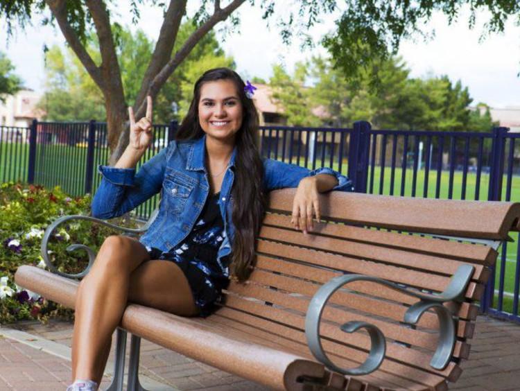 Tatum sitting on a bench on campus