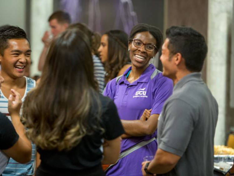 Woman in GCU shirt talking to students