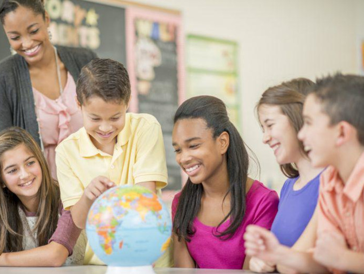 close up of students smiling around a globe