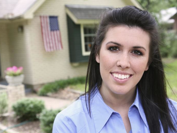 Beautiful woman in front of a house with an American flag floating
