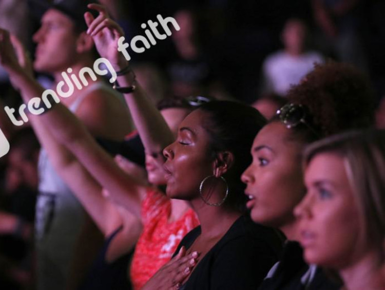 GCU students worshiping at Chapel under the Trending Faith logo