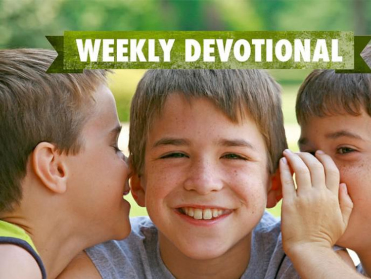 Students whispering to each other under the weekly devotional banner
