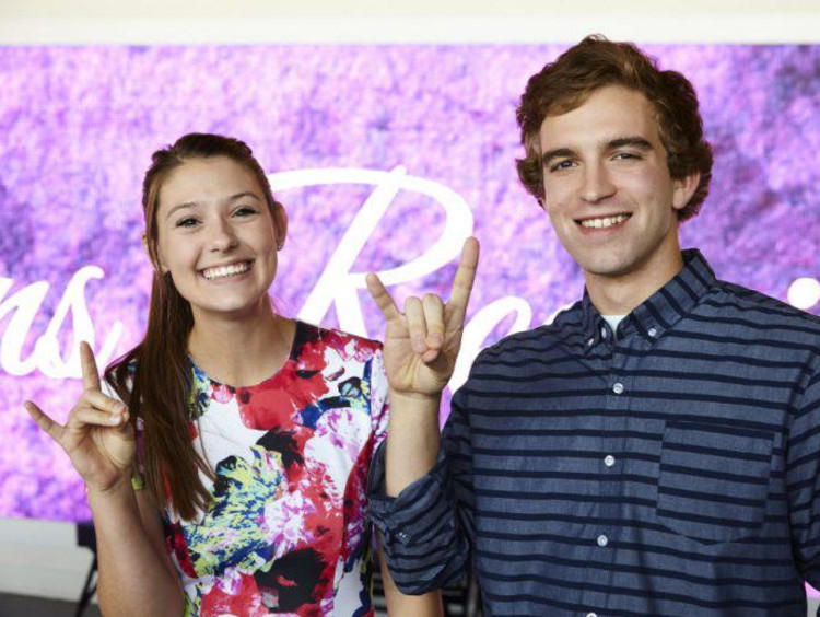 A male and female GCU student doing Lopes Up sign with their hands