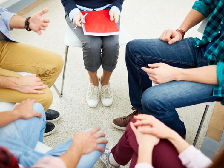 Students sit in chairs in a circle to have a team discussion