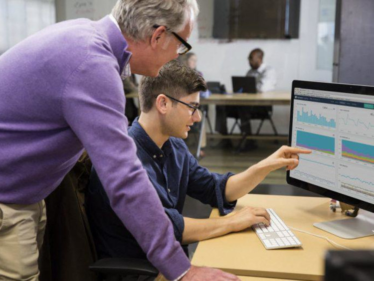 student showing professor something on a computer