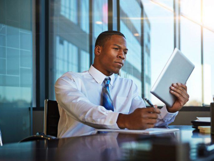 African american businessman reads technical article on tablet and takes notes