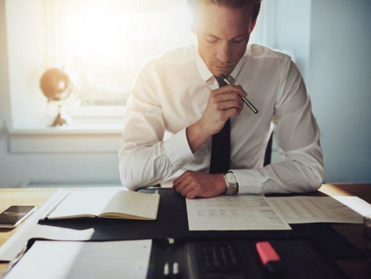 Businessman looks over financial worksheets