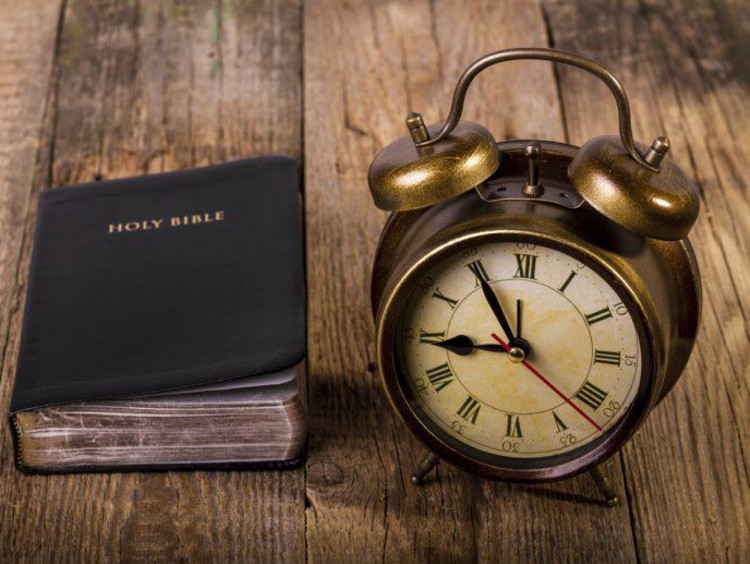 clock and bible on a table