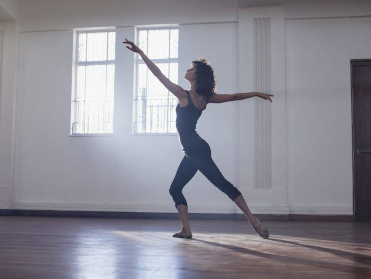 College-age woman dancing in a studio