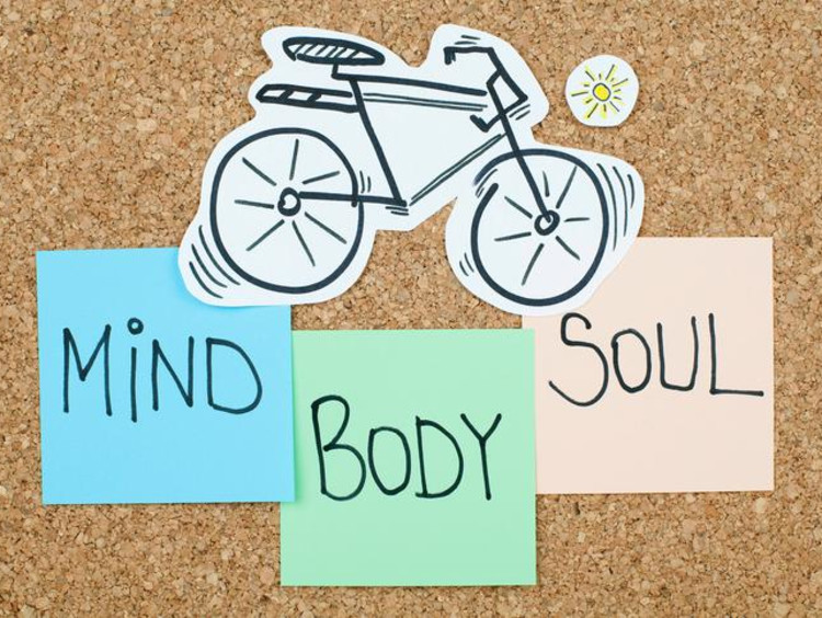 Bicycle illustration and sticky notes with Mind Body Soul are on cork board