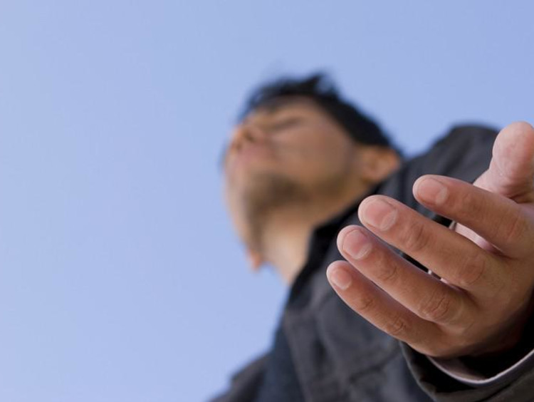Man holds his hands out with eyes closed to receive God's Blessing