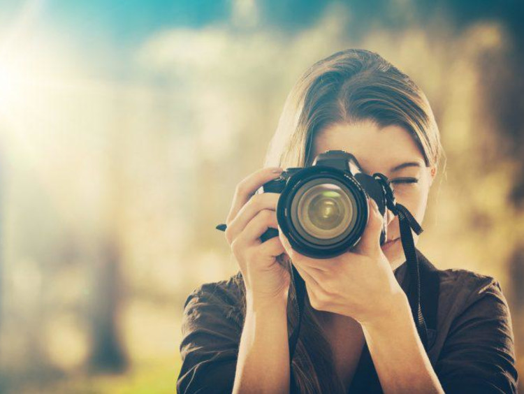girl holding camera and taking pictures