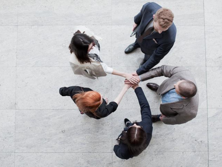 Business leaders all put their hands in the center