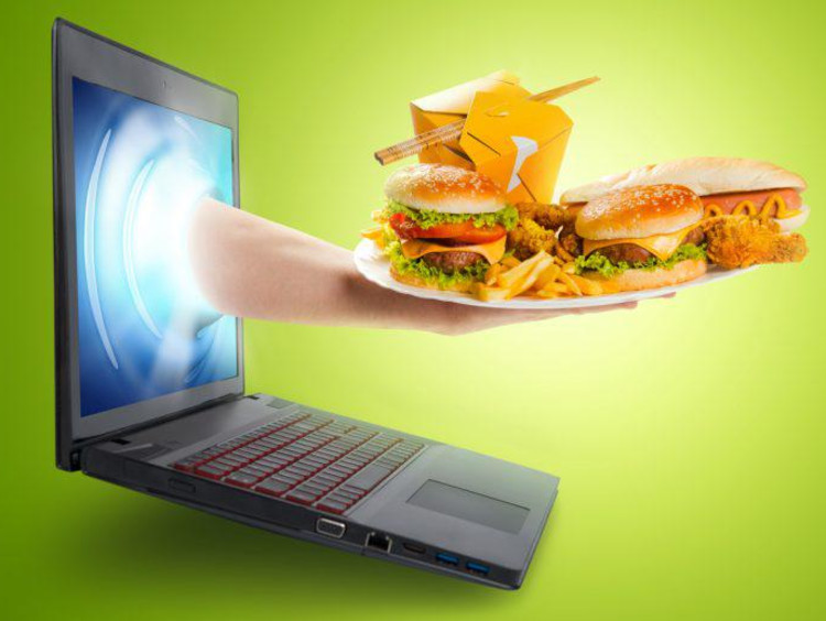 A hand with food reaching out of a computer screen