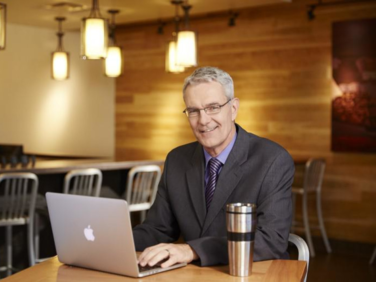 Doctoral student studies in cafe setting on laptop